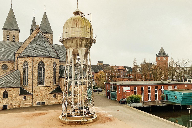 Blick über Kircheninsel mit Wasserturm, Kirche und Laden